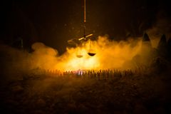 Silhouette of blurred giant scale of justice behind crowd at night with foggy fire background. Selective focus royalty free stock image