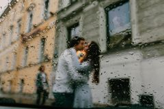 Silhouette of blurred lovers Kissing on the street of the city. View from the window of a car or cafe. Focus on the rain drops on the glass Royalty Free Stock Image