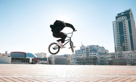 Silhouette of a bmx rider jumping against the backdrop of the sun and urban landscape on a bright summer day stock images
