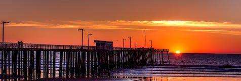 Silhouette of Boardwalk Near Body of Water Under Orange Sunset during Daytime Stock Image