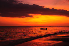 Silhouette boat at beach and sunset Stock Photos