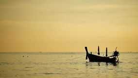 Silhouette boat excursions floating in the andaman sea with golden light. Travel Video silhouette long tail boat converted to boat excursions floating in the stock footage