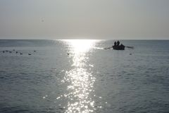 Boat with fishermen coming to seashore at sunrise after fishing offshore Royalty Free Stock Photography