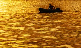 Silhouette in a boat on golden sunset Stock Photography