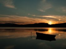 Silhouette of a boat on a lake with sunset Royalty Free Stock Image