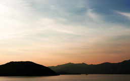The silhouette of boat and mountain with gradient sunset. The silhouette of boat and mountain with the gradient sunset Stock Image