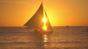 The silhouette of the boat with people sailing