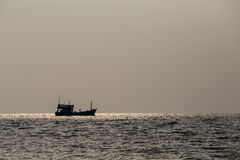 Silhouette boat and sunset over the sea water Royalty Free Stock Photos