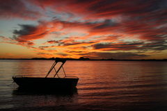 Silhouette of a boat in water sunset. A Silhouette of a small boat floating in calm waters at sunset horizontal composition stock photo