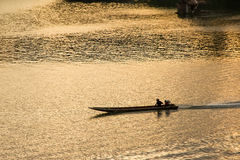 Silhouette of Boating Man boat ride in the river at sunset in Sa. Ngkhlaburi ,Thailand stock photos