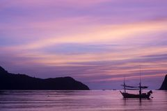 Silhouette boats and mountain in the sea with puple twilight bac Stock Photo