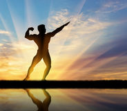 Silhouette of bodybuilder posing at sunset Stock Photo