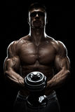 Silhouette of a bodybuilder pumping up muscles with dumbbell Royalty Free Stock Photo