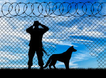 Silhouette of a border guard and a dog Stock Photo