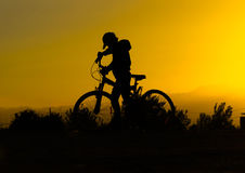 Silhouette of a boy on a bicycle at sunset Royalty Free Stock Photography