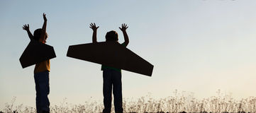 Silhouette boy with cardboard boxes of wings against sky dream o Stock Images