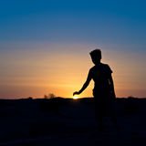 Silhouette of a boy covering the sun Stock Images
