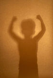 Silhouette of boy demonstrating his muscle. Silhouette of a boy demonstrating his muscle Royalty Free Stock Image