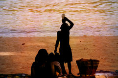 Silhouette of Boy Drinking Water on Sunny Beach Royalty Free Stock Photos