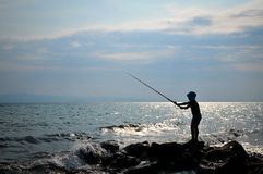 Silhouette of boy fishing. On sunset Royalty Free Stock Photos