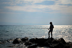 Silhouette of boy fishing. On sunset Royalty Free Stock Image