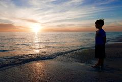 Silhouette of boy in front of a sunset, looking at the ocean royalty free stock photos