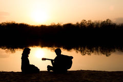 Silhouette of a boy and girl on the beach with a guitar Stock Image