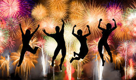 Silhouette of boy and girl jumping happy enjoy brightly colorful fireworks Stock Images