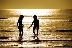Silhouette boy and girl on the sea Stock Images