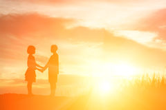 Silhouette boy and girl at sunset, romantic scene and love conce Stock Photos