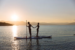 Silhouette of boy and girl on sup surf pull hands together at the ocean. Concept lifestyle, sport, love Stock Photos