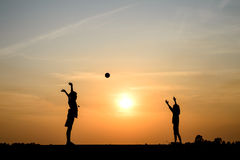Silhouette of boy and girld plying ball on sunset background Stock Photos