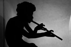 A silhouette of a boy or god Pan playing a flute. A black silhouette over the brighter wall of a boy or a mythological creature playing a flute or pipe, black stock images