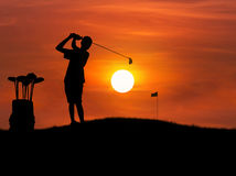 Silhouette the boy golfer hit golf ball toward the hole at sunset. With leather bag metal golf clubs Royalty Free Stock Photography