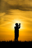 Silhouette boy hands making a heart on sunset Stock Images