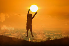 Silhouette of boy happy jumping touch  the sun Stock Image