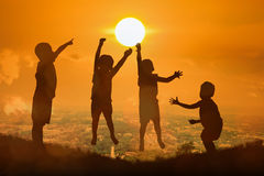 Silhouette of boy happy jumping touch  the sun Stock Photos