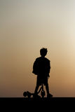 Silhouette of a boy. A silhouette of a boy on his scooter / skateboard Stock Photography
