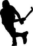 Silhouette of boy hockey player hitting ball Stock Photo