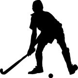 Silhouette of boy hockey player hitting ball Royalty Free Stock Photography