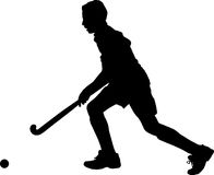 Silhouette of boy hockey player running with ball Stock Photos