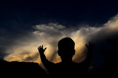 Silhouette of Boy Holding Arms Up at Sunset Royalty Free Stock Photos