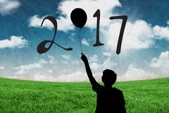 Silhouette of boy holding balloon forming 2017 new year sign Stock Image