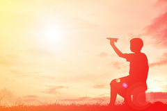 Silhouette boy holding paper rocket Royalty Free Stock Images