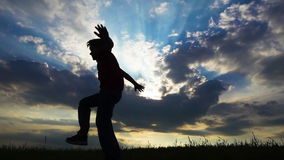 Silhouette of boy jumping on field against sunset stock video footage