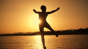 Silhouette of boy jumping from pier at sunset on the sea stock footage