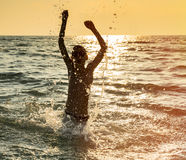 Silhouette of boy jumping in sea Stock Photo