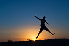 Silhouette of a boy jumping Stock Images