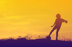 Silhouette of boy playing ball with sun set. Royalty Free Stock Image