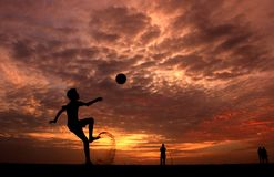 Silhouette of a Boy Playing Ball during Sunset royalty free stock photography